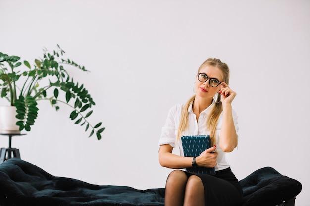 魅力的な自信を持って女性心理学者のソファに座って手で日記を持って眼鏡をかけています。