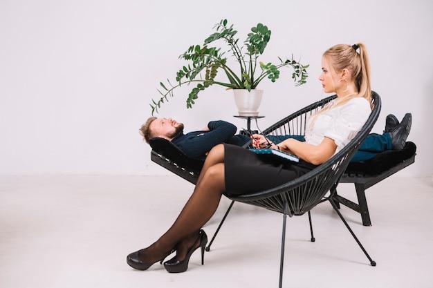 ソファに横になっている男性患者を聞いて金髪の若い女性心理学者