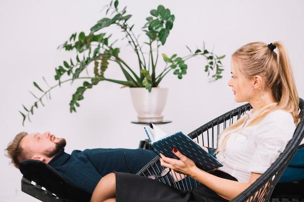クリニックでソファに横になっている男性患者を見て美しい女性心理学者