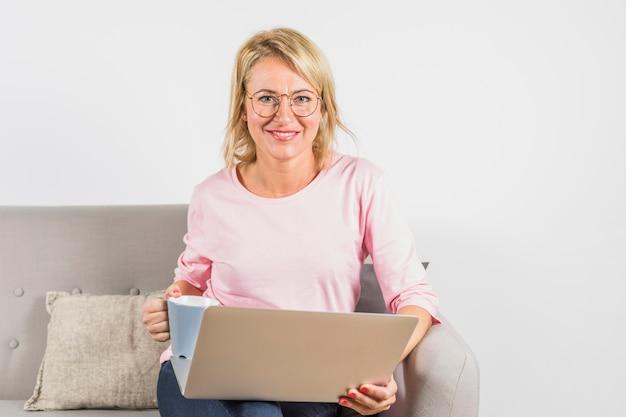 ノートパソコンとソファの上のカップとバラのブラウスで高齢者の笑顔の女性