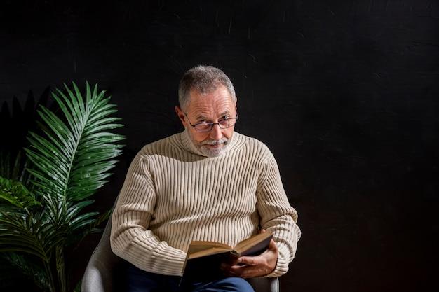カメラ目線の本を持つ老人