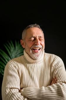 笑って組んだ腕を持つ高齢者の男性