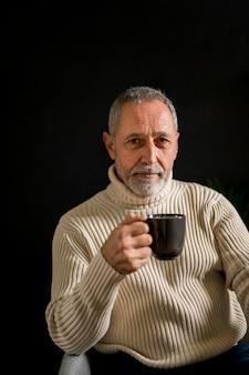 温かい飲み物のカップを持つ老人
