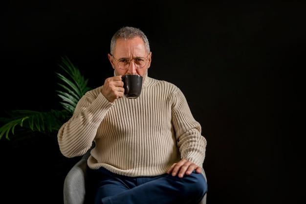 Пожилой мужчина пьет горячий напиток возле растения