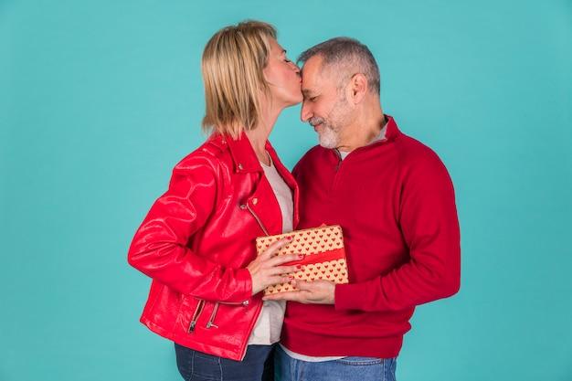 Пожилая женщина целует супруга