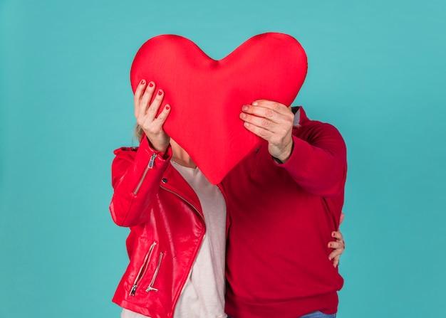 大きな赤いハートを保持しているカップル