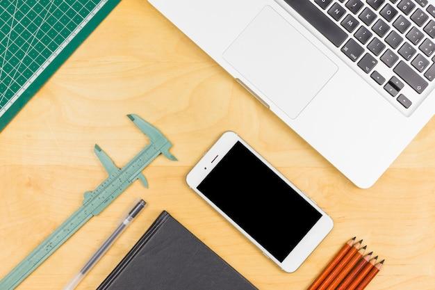 スマートフォン、メモ帳、ノギス、鉛筆の近くのノートパソコン