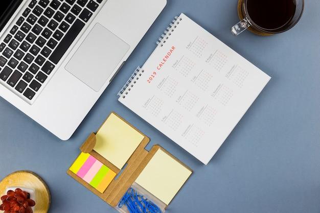Ноутбук возле календаря, наклейки и чашка с напитком