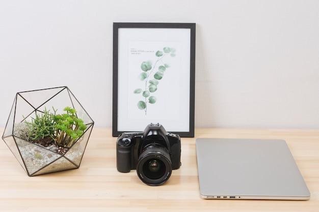 写真と木製のテーブルの上のカメラとノートパソコン