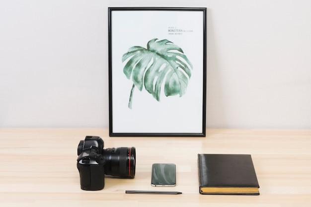 スマートフォンとテーブルの上のノートとカメラ