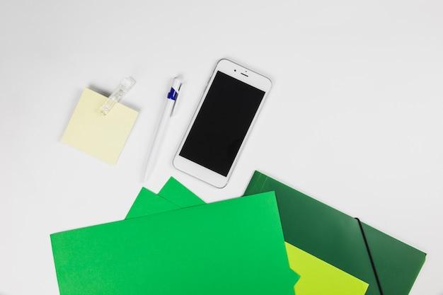 Смартфон с наклейками и ручкой на столе