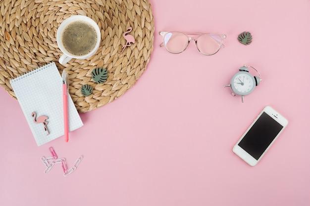 コーヒーカップとテーブルの上のメモ帳を持つスマートフォン