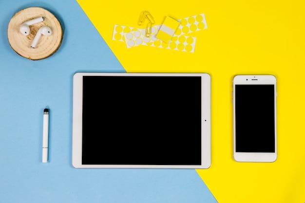 タブレットとイヤホンのテーブルの上にスマートフォン