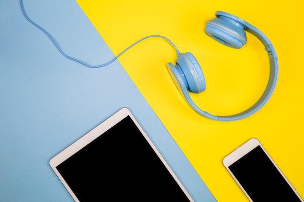 タブレットとヘッドフォンテーブルの上のスマートフォン