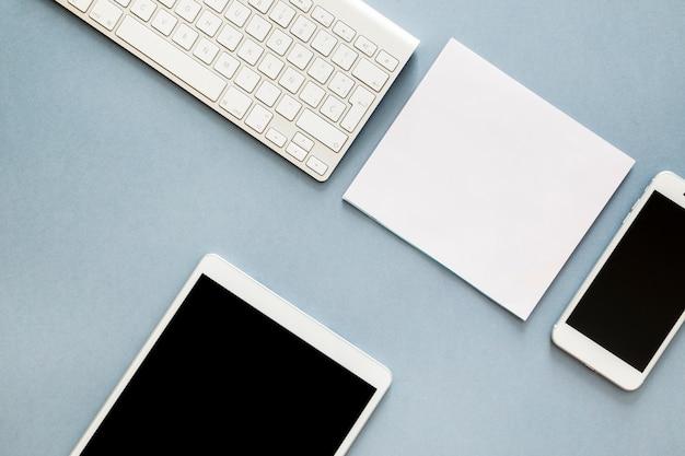 キーボードとスマートフォンをテーブルの上にタブレットします。