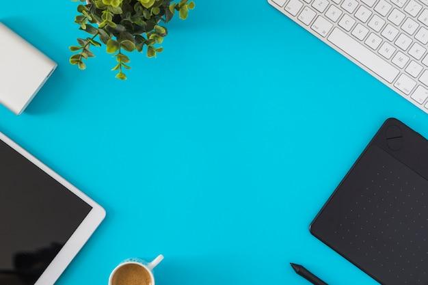 青いテーブルの上のキーボードとタブレットします。