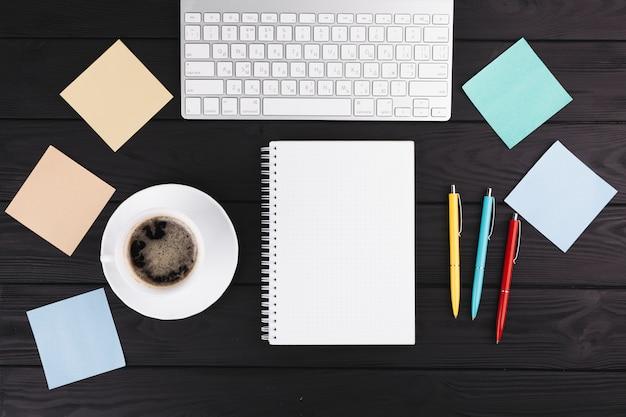 Ручки возле тетради, чашка на блюдце, бумага и клавиатура