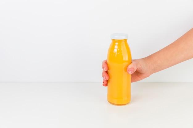 白い背景と新鮮なオレンジジュースの瓶