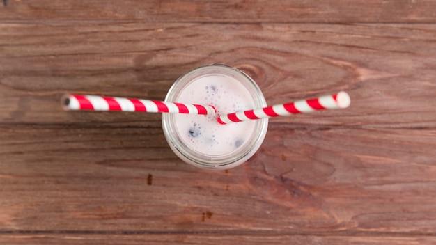 Плоский лежал молочный коктейль на деревянном столе