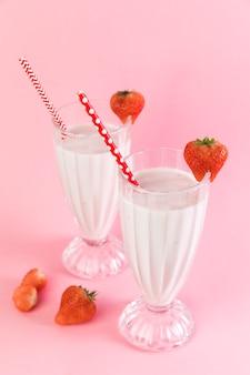 ピンクの背景とイチゴのミルクセーキのグラス