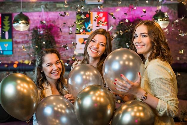 Молодые подруги держа серебряные воздушные шары наслаждаясь в партии
