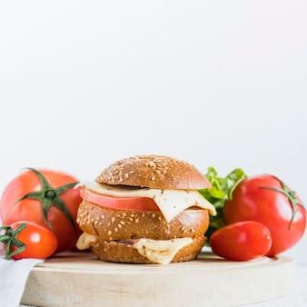 トマトの近くのチーズのサンドイッチ
