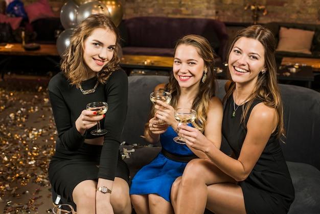 パーティーで飲み物のグラスと笑顔の魅力的な女性の友人のグループ