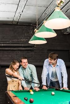 幸せな若い男性と女性がクラブでビリヤードをプレイ