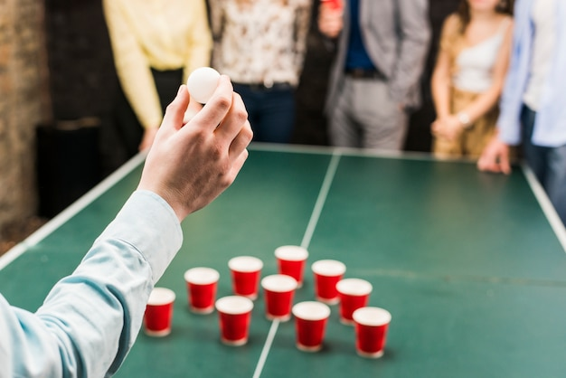 ビール卓球ゲームのためのボールを持っている人の手のクローズアップ