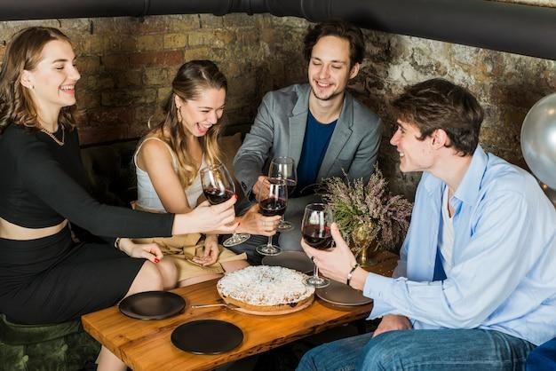 幸せな人々の夜のパーティーで乾杯のグループ