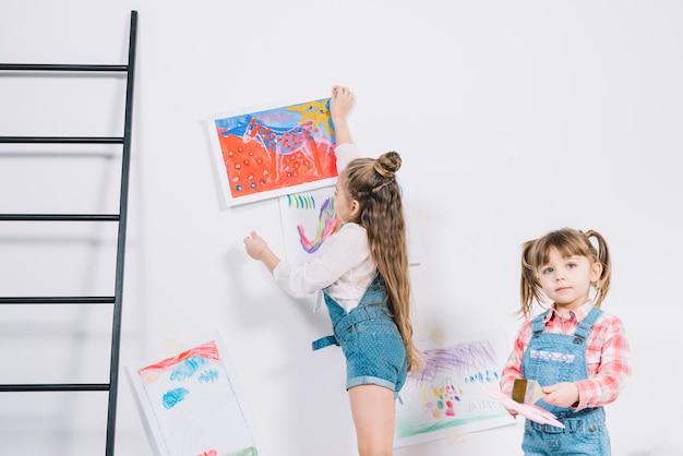 壁に絵をぶら下げ小さな女の子