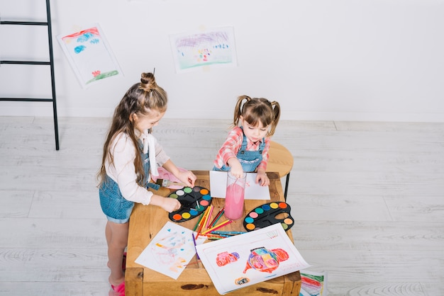 木製のテーブルでアクワレルで絵を描く二人の少女