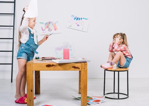 かわいい女の子の絵画座っている女の子の椅子