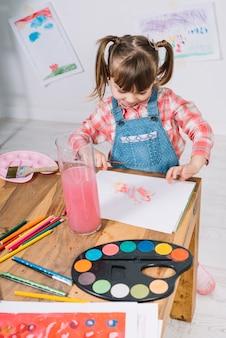 テーブルで紙の上のアクワレルと絵画かわいい女の子