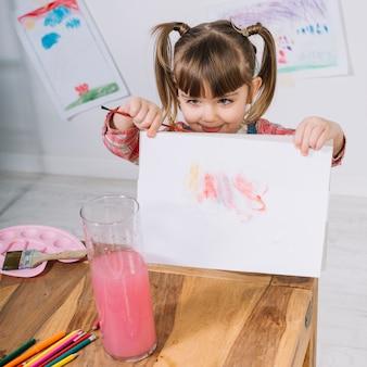 紙の上の絵を示す小さな女の子