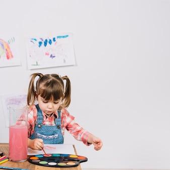 木製のテーブルでアクワレルで絵の少女