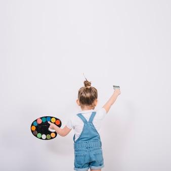ブラシで小さな女の子絵画白い壁