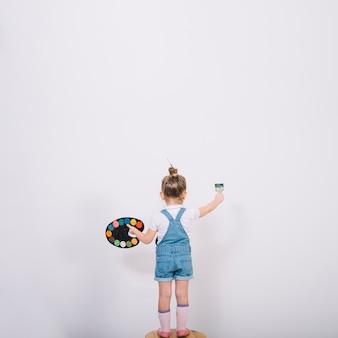 椅子とブラシで絵の壁の上に立っている女の子