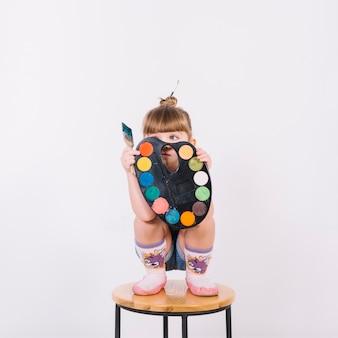 椅子の上のパレットで顔を覆っている小さな女の子