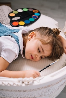 明るいアクワレルパレットが付いているソファーで寝ている少女