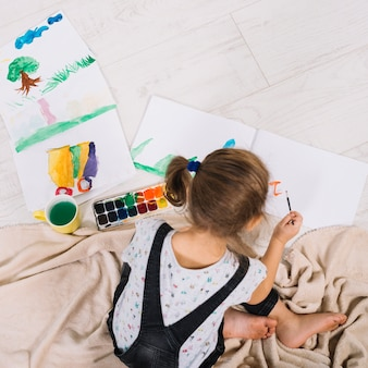 床にアクワレルと絵画の小さな女の子