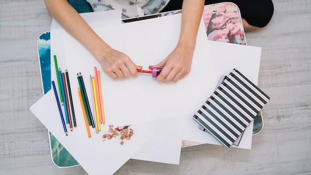 女性の紙と鉛筆のセットを持つテーブルで鉛筆をシャープ