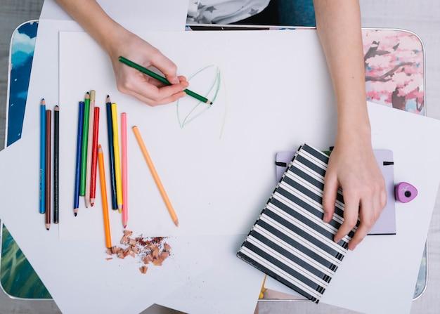 鉛筆のセットを持つテーブルで紙に絵を描く女
