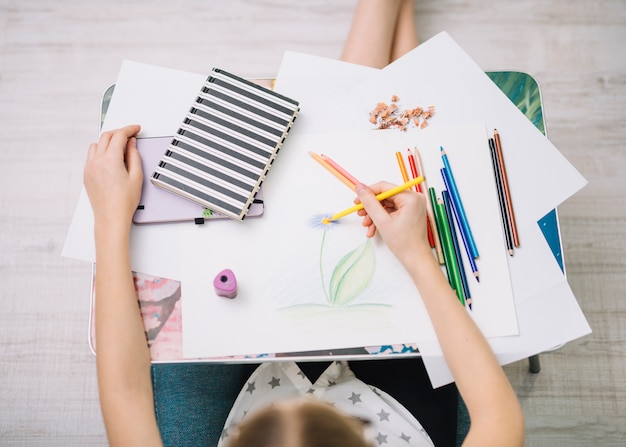 鉛筆のセットを持つテーブルで紙に絵を描く少女