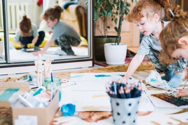 ボックス、鉛筆、紙の間の床に絵を描く女の子