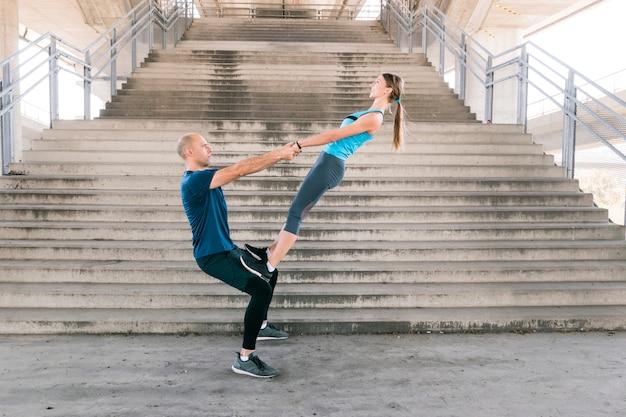 階段の前で運動をしている陽気な若いカップルの側面図