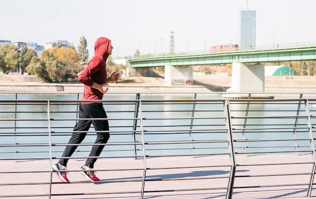 湖の近くを走っているスエットシャツパーカーを着ているオスの運動選手