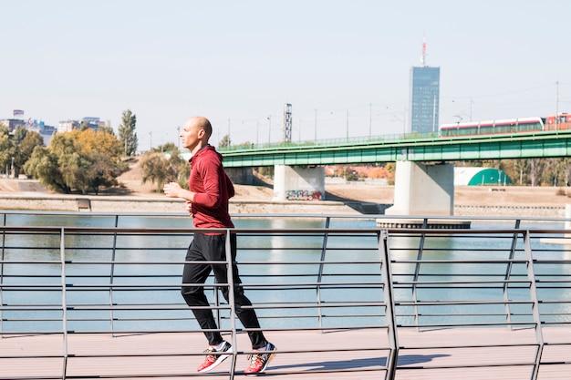 川の近くを走っている白人男性ランナー
