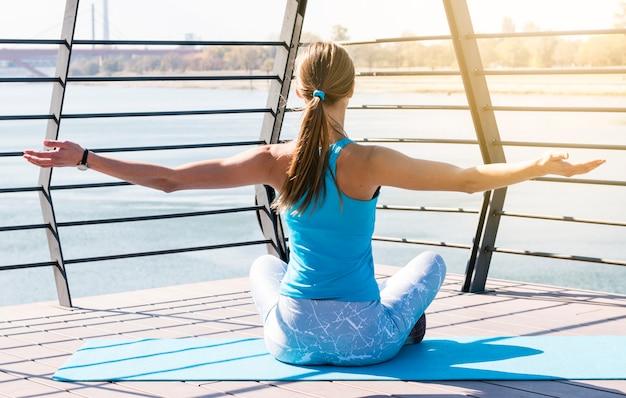 橋の上に座って彼女の手を伸ばして運動マットの上に座っている若い女性の背面図