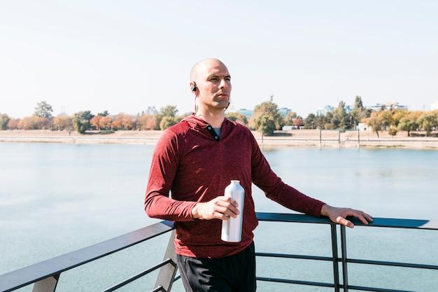 水のボトルを手で押し、湖の近くに立っている若い女性の肖像画